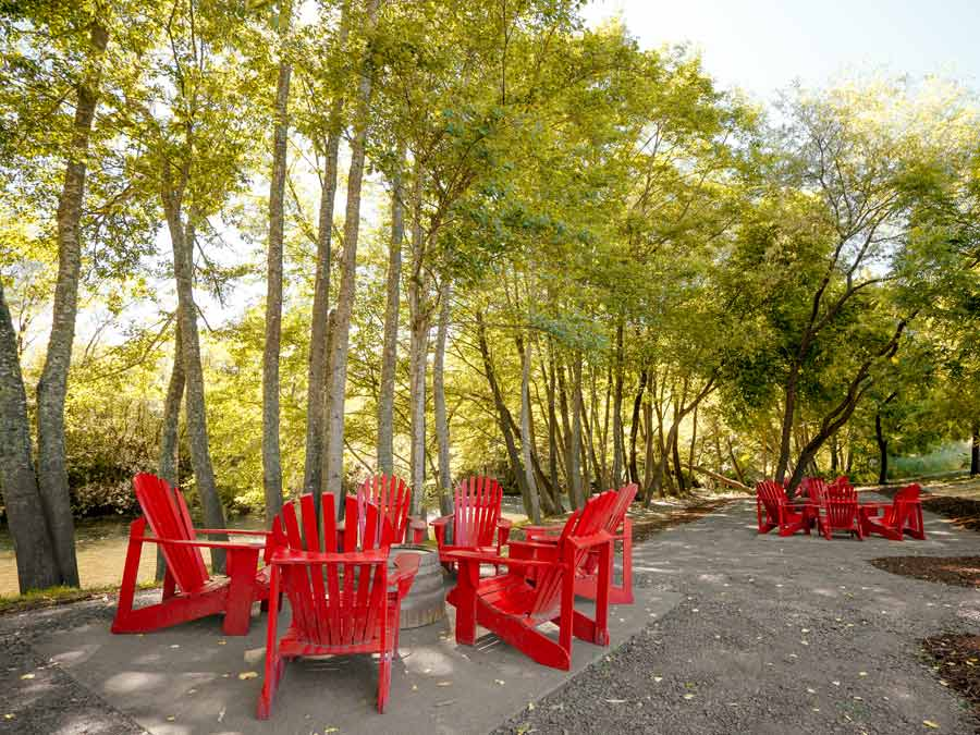 Red adirondack chairs line Dry Creek at Truett-Hurst Winery, Healdsburg