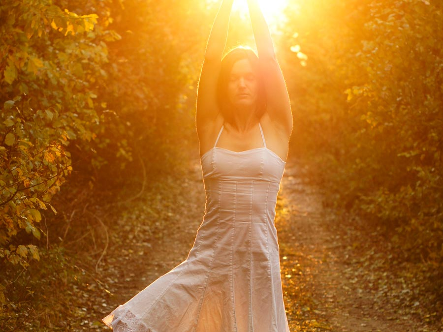 A woman stretches with the sun setting behind her among rown of grape vines