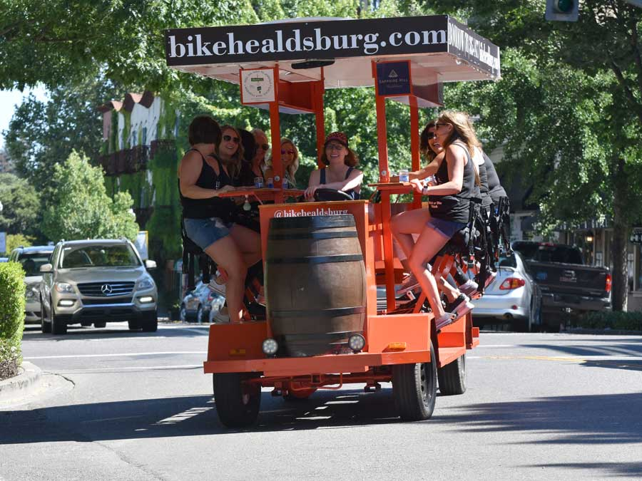 A groups rides the party bike in downtown Healdsburg with Bike Healdsburg