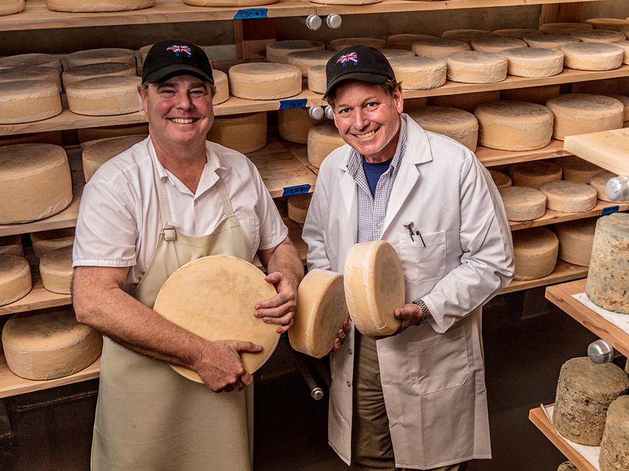 Two cheesemongers hold their wares surrounded by columns of cheese in The Barlow in Sonoma County