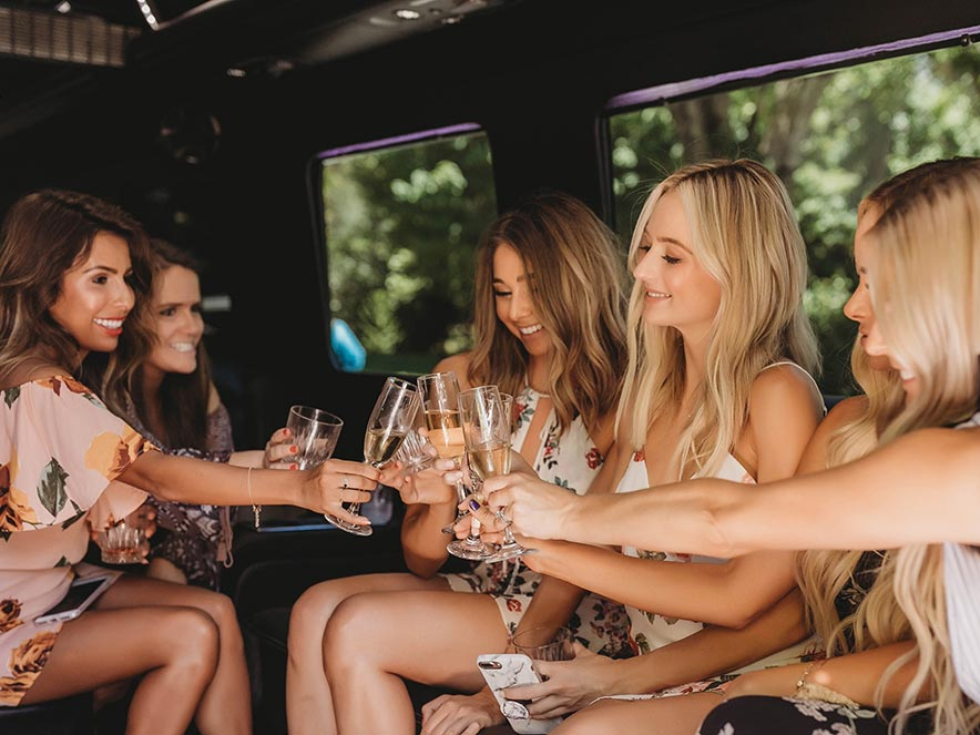 Women toast with champagne in a Pure Luxury limousine