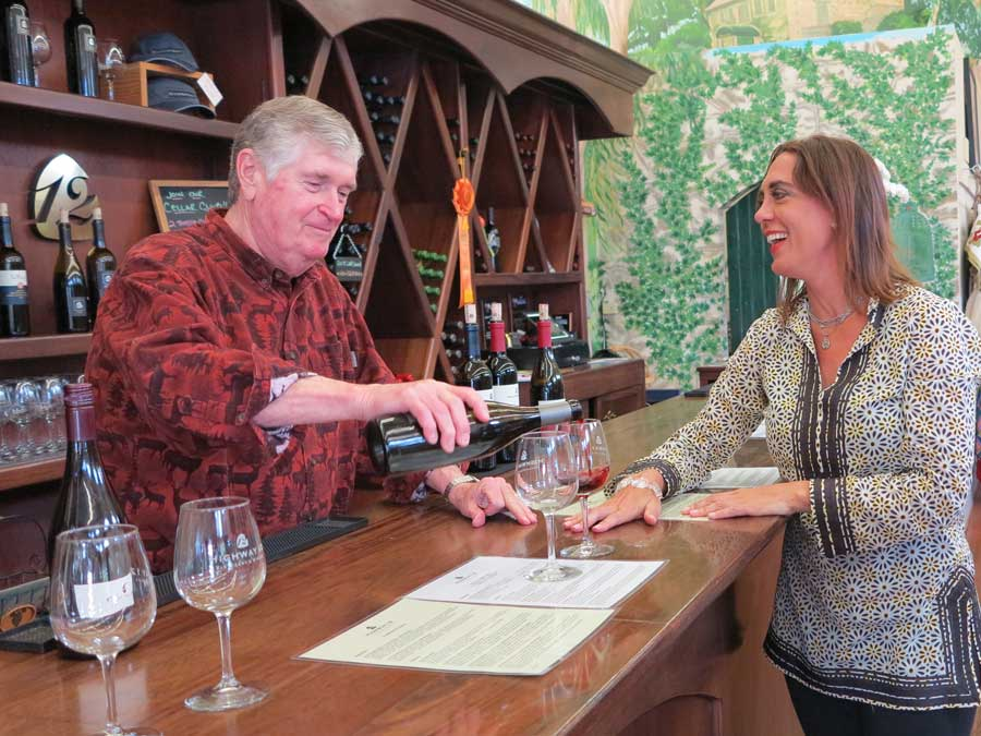 A woman is poured a glass of wine at a tasting bar in Sonoma County