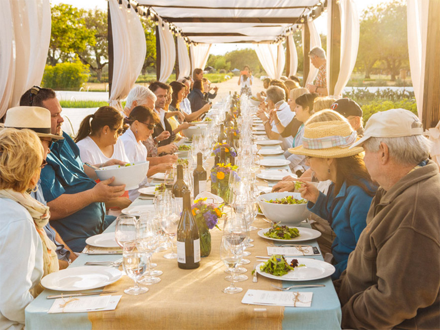 A group of people share a meal at a banquet table at Kendall-Jackson Family Winery