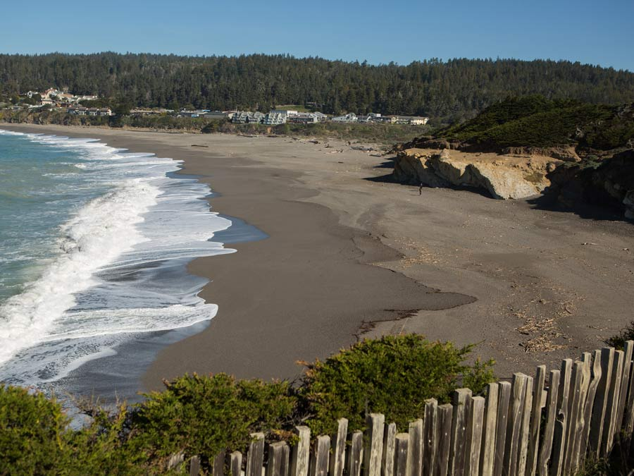 A sandy beach is surrounded by jagged cliffs in Sonoma County