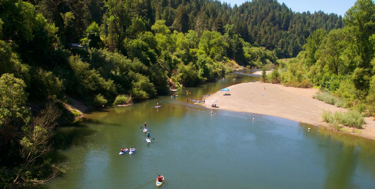 People paddle and swim in the Russian River, Sonoma County