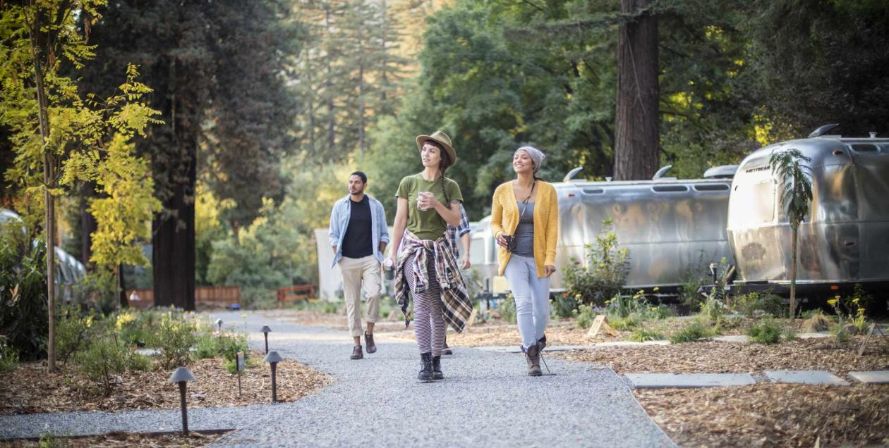 Two women walk down a path between luxury Airstreams at Autocamp in Guerneville, Sonoma County