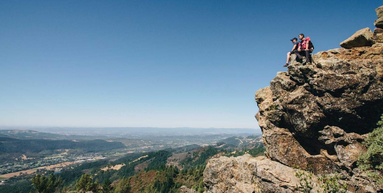 Two hikers sit on a rock overlooking the valley below in Hood Mountain Regional Park, Sonoma County, California
