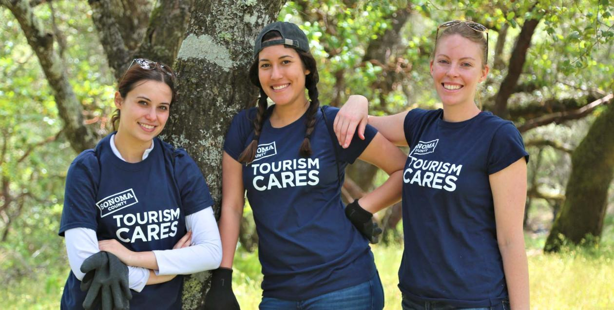 Three women wearing Tourism Cares t-shirts in the woods.