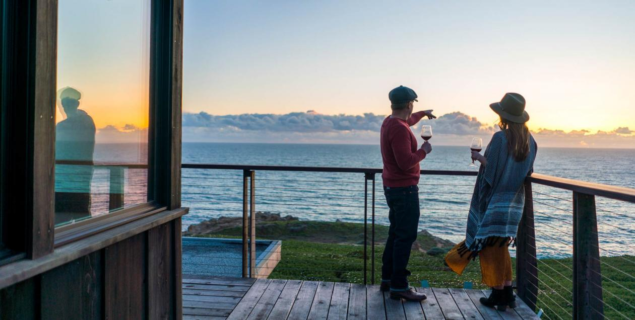 A couple stands on the deck outside of an ocean view room at Timber Cove Resort, Sonoma County