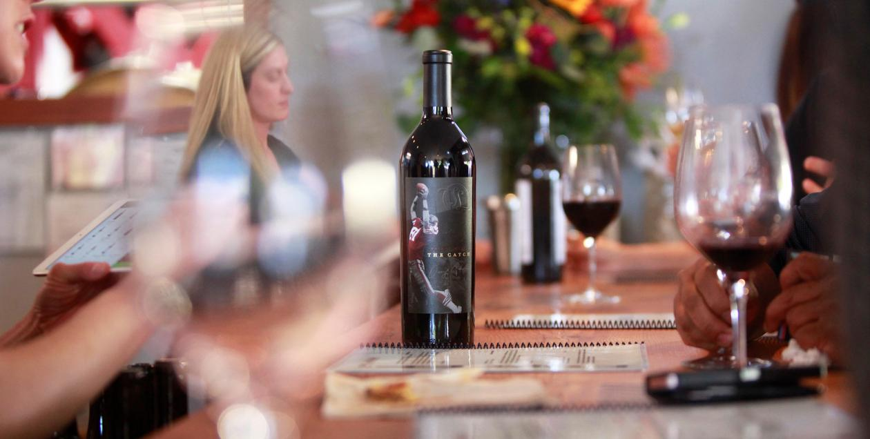 A wine bottle sits on the counter at a tasting room with glasses blurred out in the foreground, Topping nad Legnon Tasting Room, Sonoma County, California