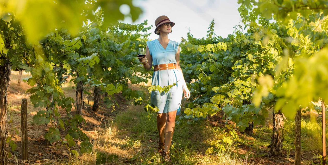 A woman in a blue dress and a straw hat walks confidently through a vineyard in Sonoma County, California