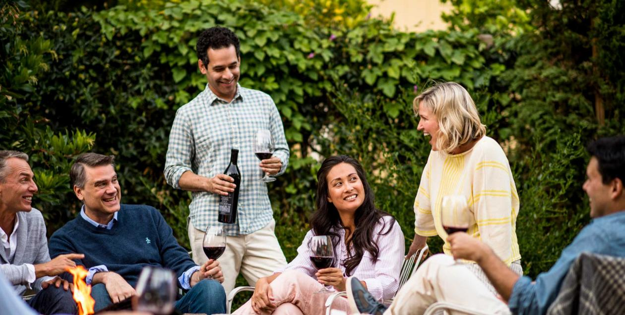 group of friends drinking wine around fire pit at Farmhouse Inn in Sonoma County