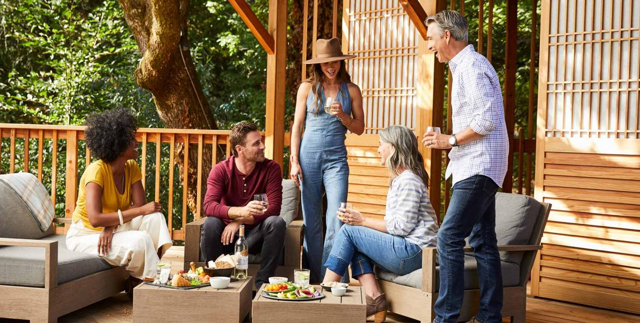 Friends gather around a vegetable platter on a wooden deck in Sonoma County