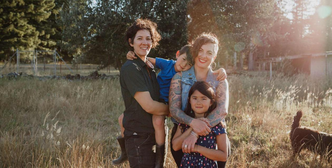 Two moms and their children stand in a field at Radical Family Farms