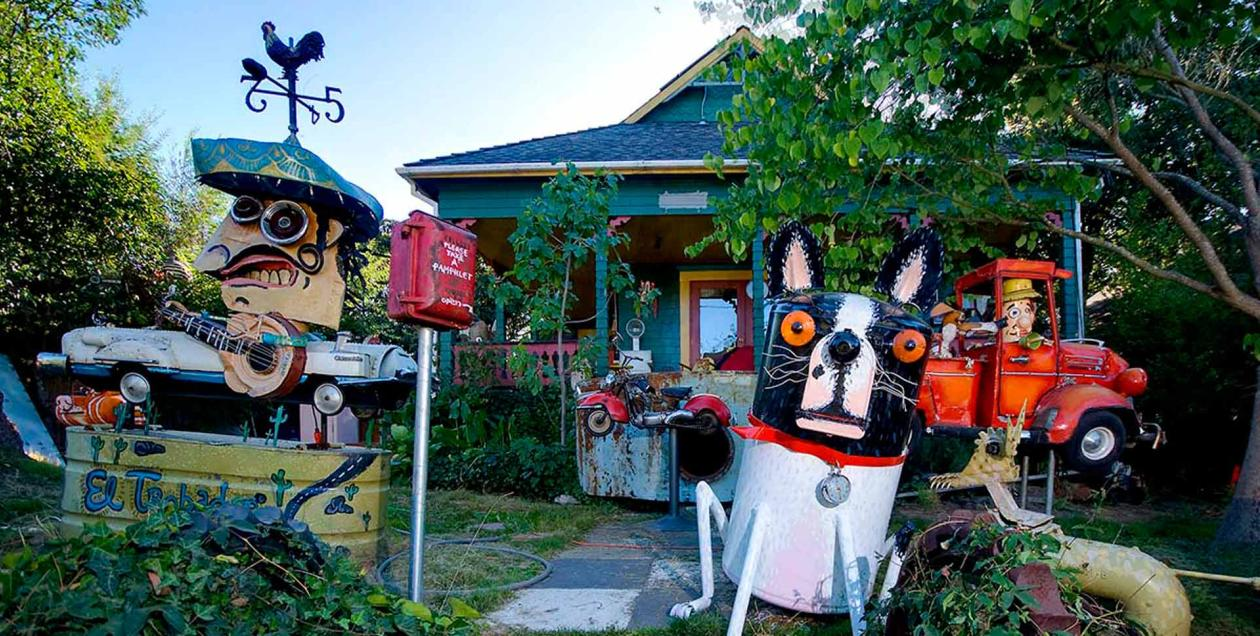 A sculpture of a dog and other metal sculptures in front of a house