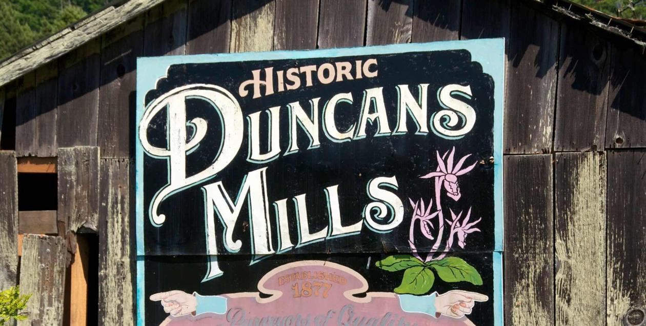 A sign for Historic Duncans Mills on the side of an old, wooden building