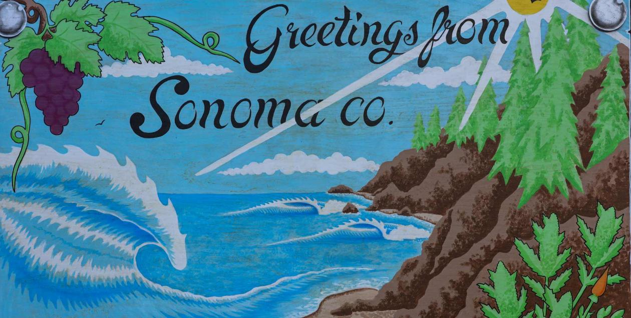 A mural has the ocean, redwoods and grapes and says Greetings from Sonoma County