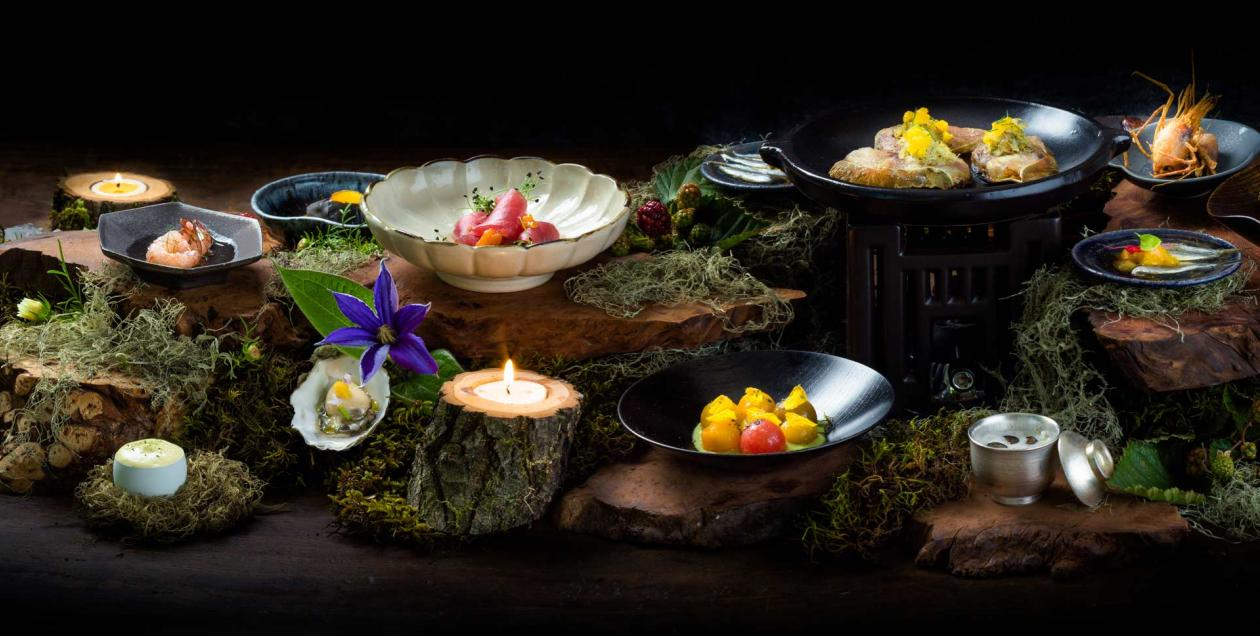 Artfully plated food with decorations of moss and candles
