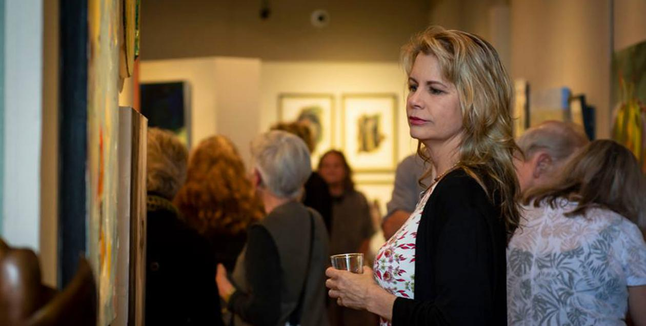 A person holds a glass and looks at art on the wall
