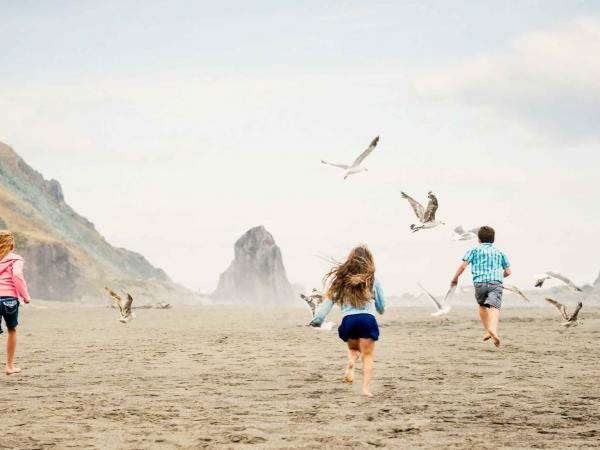 Three children run down the beach, making the seagulls go into flight on the Sonoma County Coast