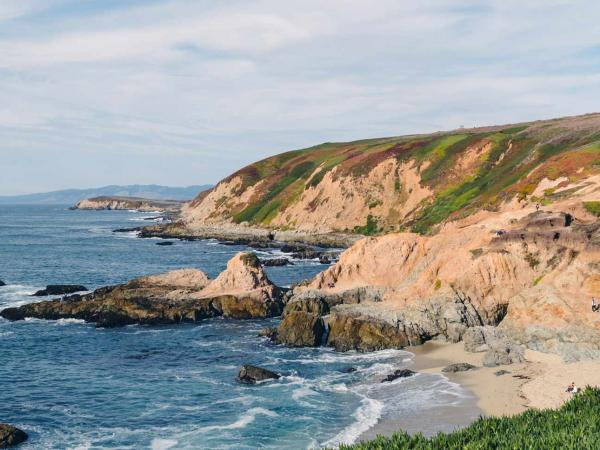 The verdant green and beige of the Bodega Head rock formations rises above the crystaline blue waters of the Pacific Ocean in Bodega Bay, Sonoma County, California