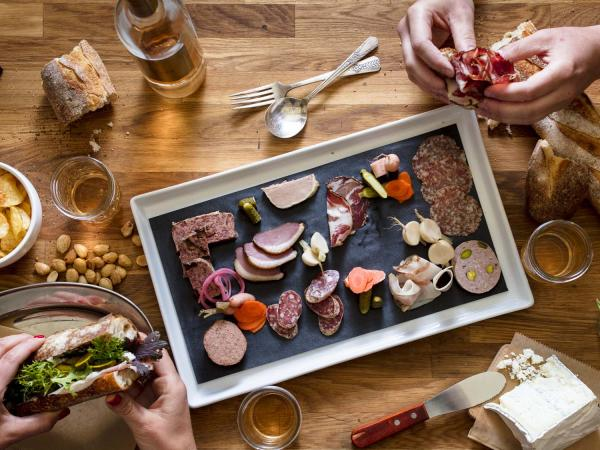 Two people enjoy a charcuterie plate and sandwiches at Thistle Meats