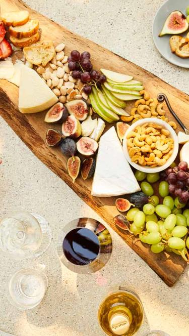 A platter or fruit, nuts, and cheese from above, and wine too