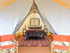 A glamping tent has two orange directors chairs outside of it