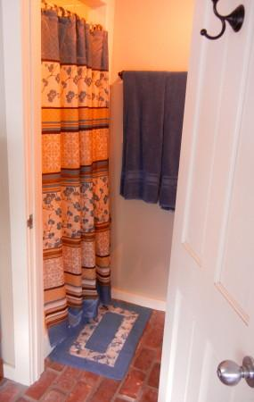 Bathroom with tiled shower & commode. Photo 11