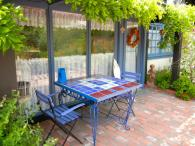 Table & chairs under wisteria overhang. Photo 12