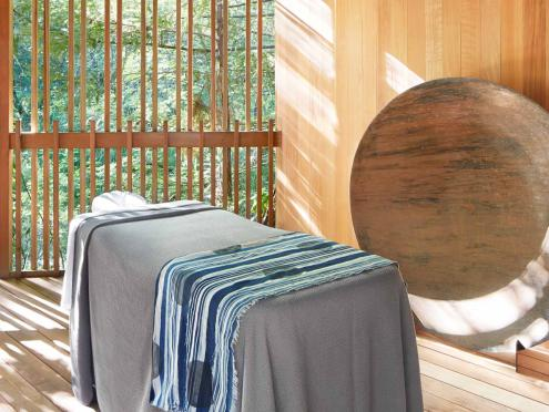A massage table sits in a meditation room with greenery in the background at Gaige House and Ryokan in Sonoma County, California