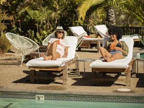 Two girls lounge at the pool at boon hotel + spa in Sonoma County