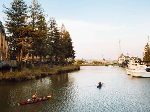 Two kayakers travel down the Petaluma River at sunset in Sonoma County