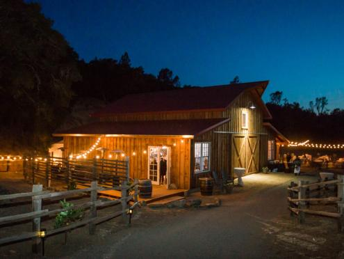 The barn venue for weddings at The Ranch at Lake Sonoma comes alight as the sun sets.