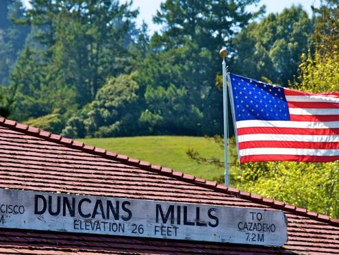 An American flag flies above a building that has a sign that says Duncans Mills elevation 26 feet in Sonoma County