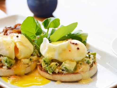 Eggs benedict with avocado sitting on a table with a cup of coffee