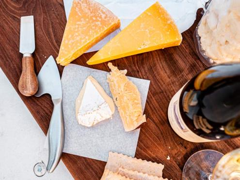 Wedges of cheese, crackers, a cheese knife, and a glass of wine from above