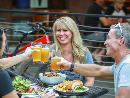 Three people cheers with beer at a patio table
