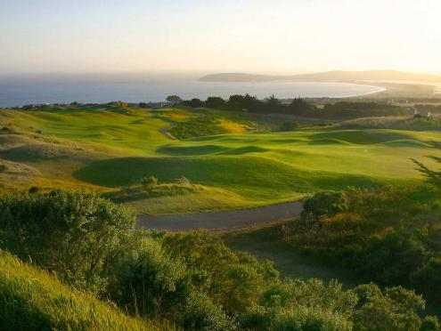 A golf course along the coast at sunset