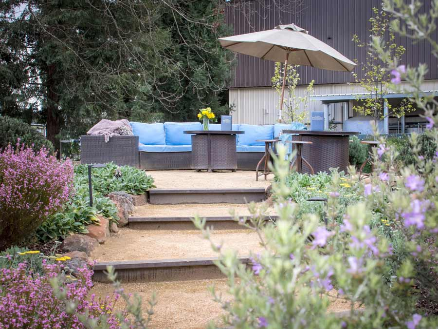 Steps lead up to a comfy seating area shaded with umbrellas and surrounded by flowers